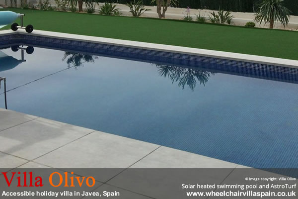 Solar heated swimming pool surrounded by terrace and AstroTurf