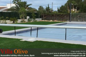 Swimming pool area surrounded by AstroTurf at Spanish Holiday Villa for wheelchair users